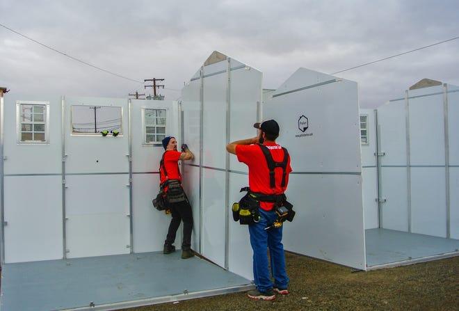 Deux employés de Pallet, l'entreprise qui fabrique et installe des abris d'urgence temporaires, assemblent l'une des unités le 5 novembre 2020, à The Dalles, Oregon. Les abris préfabriqués ont été achetés et fonctionneront en partie avec les fonds de la loi CARES.