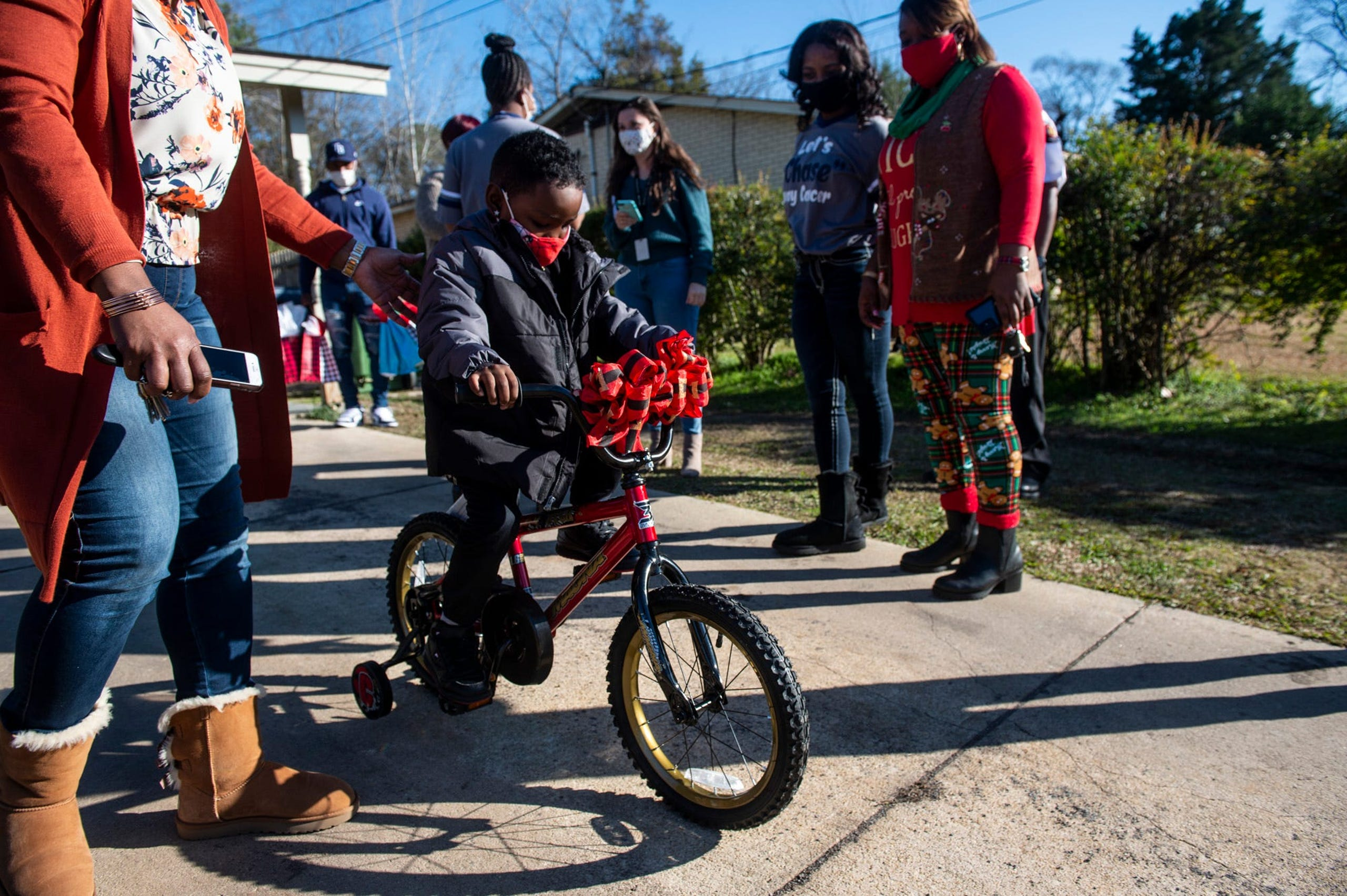 Caulio Mclemore tests out his new bike in Montgomery, Ala., on Monday, Dec. 21, 2020. Caulio is battling Leukemia and Chase Perine, his classmate decided to help get him presents for Christmas.