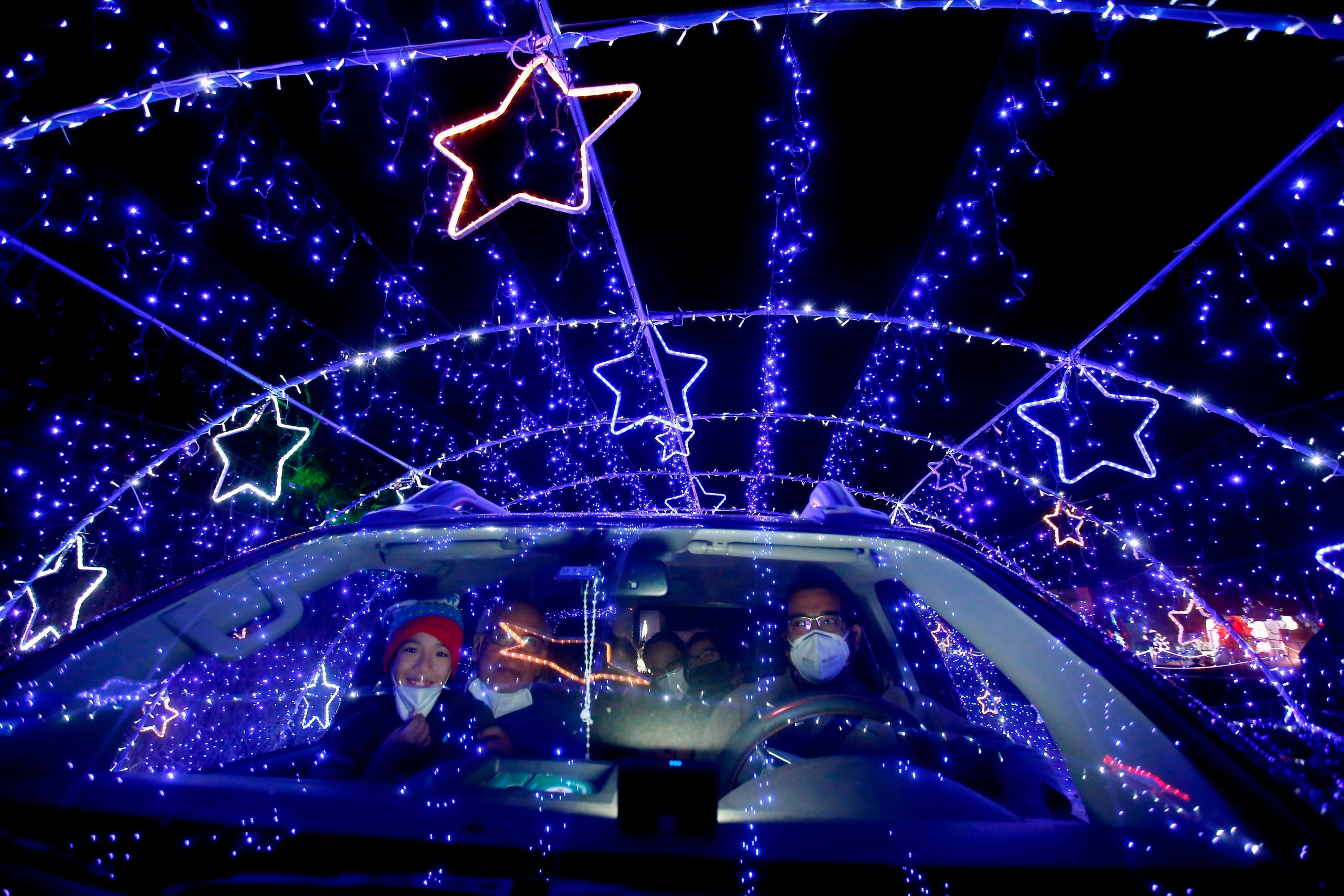 "A family observes the Christmas lights as they pass through the ""Santa's Village Drive-Thru"" in Guadalajara, state of Jalisco, Mexico, on Dec. 20, 2020."