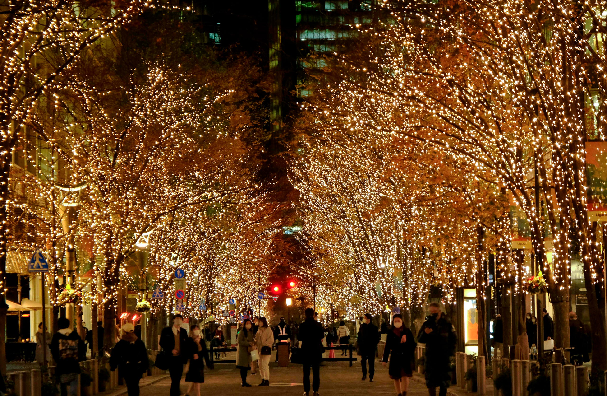 "People walk under winter-themed illumination, lit by approximately 1.2 million ""champagne gold"" LED lights as part of seasonal decorations, in the Marunouchi business district of Tokyo on Dec. 21, 2020."