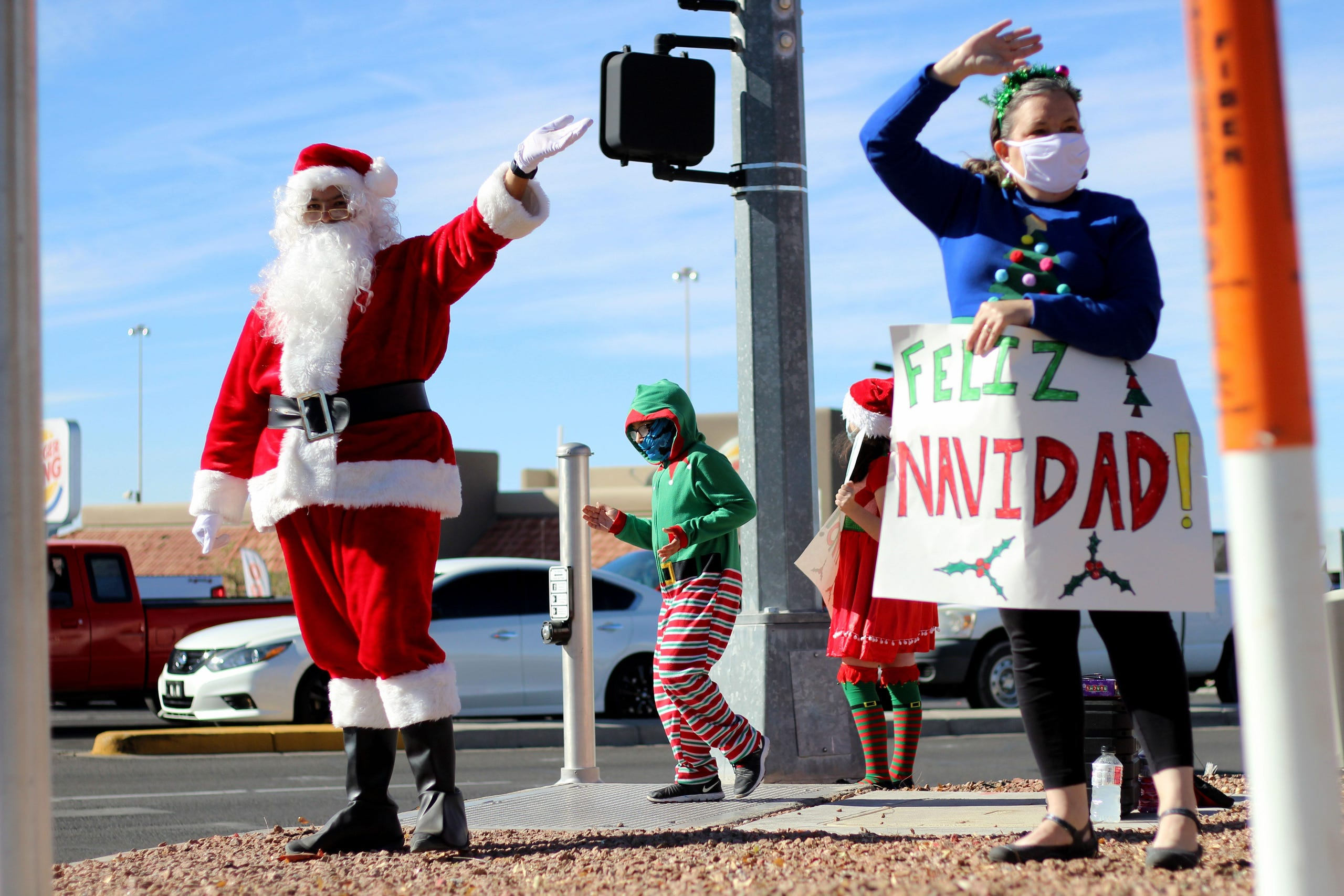 From left, Dennis, Kephas, Miranda and Toni Garcia stand at the corner of Lohman Avenue and Telshor Boulevard to spread holiday cheer on Dec. 21. The family blasts holiday music and waves to cars as they drive by. Dennis said he wore the costume to read to his wife Toni's first-grade class last week. The family then decided to head out to the busy intersection and spread Christmas cheer.Curcessanta10