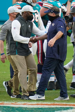 Patriots coach Bill Belichick, right, congratulates his former assistant, Dolphins coach Brian Flores, after a game.