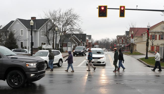 A group crosses Library Street at state Route 303 in Hudson.