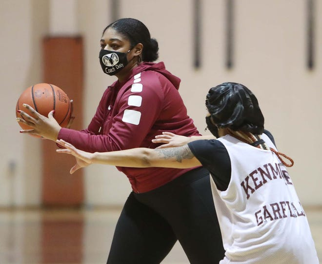 Paris Caldwell, the basketball coach for the Kenmore-Garfield girls basketball team passes the ball by player I'anna Lopp during a recent practice. Caldwell took over as coach after her mother, Yontami Jones, recently died from cancer. [Karen Schiely/Beacon Journal]