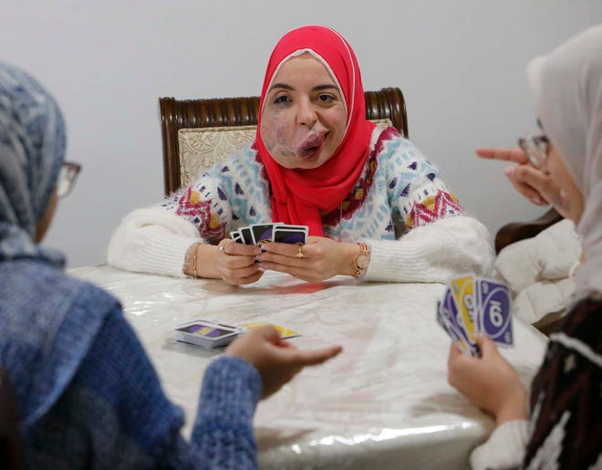 Lamise ElBetar, center, plays a card game last month with sisters Eman Hassan, 21, left, and Toqa Hassan, 24, at the home of the sisters' parents Ghada Awad and Nasser Razek in Akron. A last-minute job offer is allowing the University of Akron grad to stay in the United States.