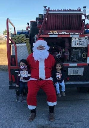 Santa gives out Christmas presents to children in Orange Grove.