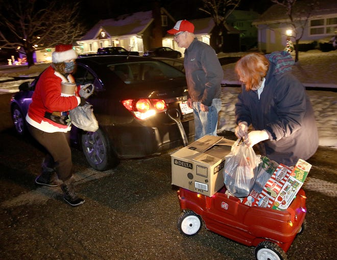 Pam Webb, right, and Rick Webb, center, loaded Chrstimas gifts and food into a wagon Cathy Brookes, left, will take back to the Shonk family home across the street during Cram-the-Cruiser Night sponsored by Shonk Family Lights and the Alliance Fraternal Order of Police Lodge #73, December 18, 2020. Ed Hall Jr, Special to The Review