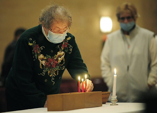 Doris Livengood places a lighted candle in memory of her late husband, Dick Livengood, at the conclusion of a Blue Christmas service Sunday, December 20, 2020, at First Christian Church.