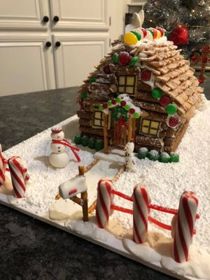 """The Rogers Family received first place in the family category of the gingerbread decorating contest with their """"Cozy Christmas Cabin."""""""