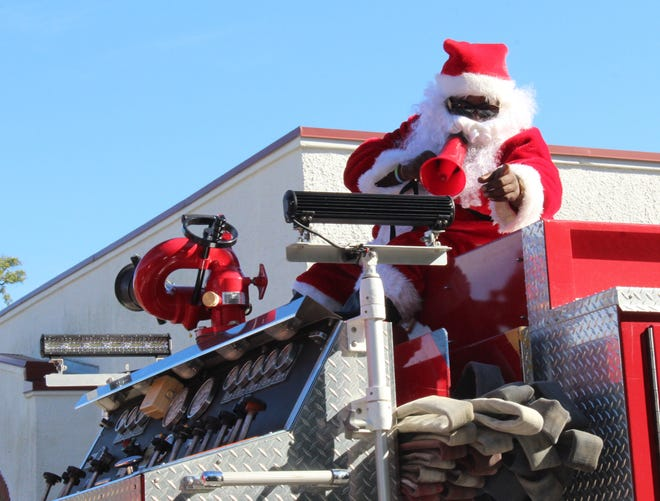 Santa used a megaphone from atop the fire truck to address the children who awaited his arrival