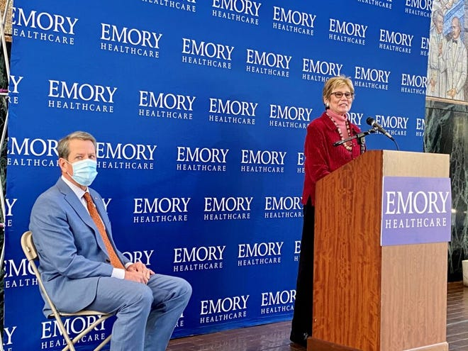 Georgia Public Health Commissioner Dr. Kathleen Toomey, right, gives updates on COVID-19 vaccine distribution and the worsening winter outbreak, alongside Gov. Brian Kemp, at Emory University's Woodruff Health Sciences Center in Atlanta Tuesday.