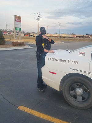 A Bartlesville Police Officer wears a mask while processing a traffic stop.