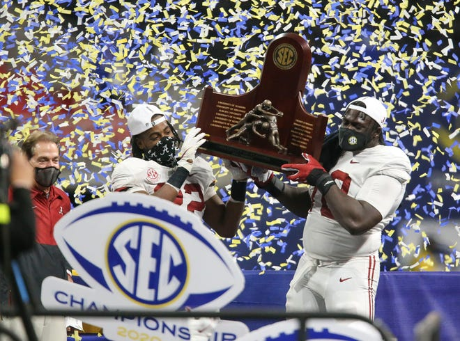 Alabama coach Nick Saban, left, looks on as running back Najee Harris (22) and offensive lineman Alex Leatherwood (70) lift the Southeastern Conference football trophy in celebration after Alabama's 52-46 victory over Florida in the league title game Saturday at Mercedes-Benz Stadium in Atlanta.
