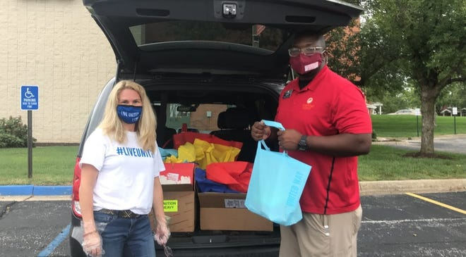 Heart of Missouri United Way finance manager Laura Scarborough and Turning Point managing director Darren Morton with Care Kits assembled by volunteers in September.