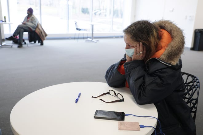 Linda Frazier sits inside a warming station on Tuesday at the Columbus Metropolitan Library main branch in Columbus. Frazier arrived in Columbus six days earlier from Tennessee and was kicked out of her housing earlier in the day. The station recently opened to give people who are  homeless a respite from the cold weather.