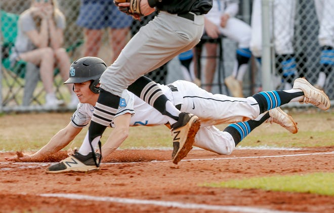Oak Grove's Levi Perrell slides into home to score a run against Ledford on March 13, the last day of high school sports in North Carolina for the 2019-20 season. [Michael Coppley for The Dispatch]