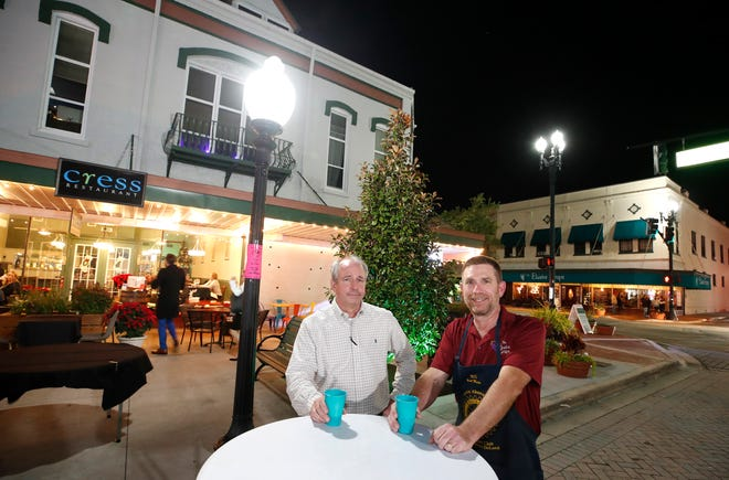 Tom Brandt, majority owner and general manager of Cress Restaurant, and Bill Budzinski, owner of the wine bar and restaurant The Elusive Grape, catch up at one of the high-top tables set up on a closed West Indiana Avenue on Friday, Dec. 18, 2020. Both businesses are offering the special to-go cups for downtown DeLand visitors who want to have a cocktail or glass of wine as they peruse downtown's shops.