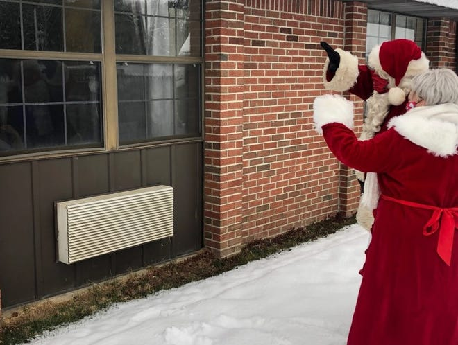Santa and Mrs. Claus wave to a resident and staff member at Houghton Rehabilitation and Nursing.