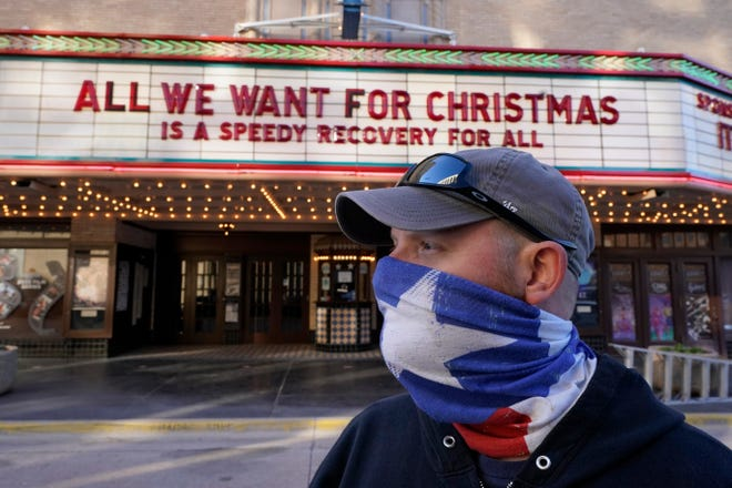 Employee Grayson Allred poses for a photo after putting up a message on the front marquee at the Paramount Theatre on Dec. 16 in Abilene. The theatre has closed down operations indefinitely due to rising cases of COVID-19 in the city.