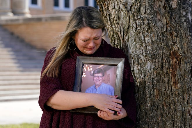 Katie Riggs Maxwell begins to cry as she hugs a portrait of her father Mark Riggs while posing for a photo, Dec. 16, on the campus of Abilene Christian University in Abilene. Mark Riggs, who was a professor at the school, died last Monday of COVID-19. (AP Photo/Tony Gutierrez)
