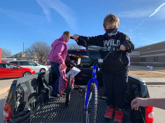 Zoie Kirk and Tucker Etienne unload bikes to donate to the Salvation Army's Christmas gift program.