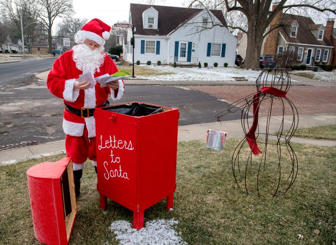Santa Claus looks over a set of letters he pulled from the mailbox in the front yard of Eric Sparks' home at 327 N. Kickapoo Terrace in West Peoria. Kids can drop off their letters and Sparks makes sure Santa reads them and responds.