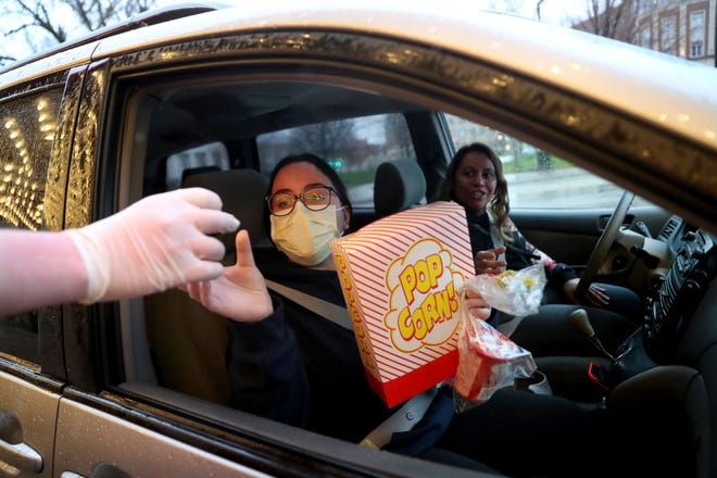 Customers Jessica Rodriguez and her mother, Maryland Rodriguez are handed their popcorn at the curbside pickup line at the Pickwick Theatre in Park Ridge on Saturday, April 25, 2020. (Chris Sweda/Chicago Tribune/TNS)