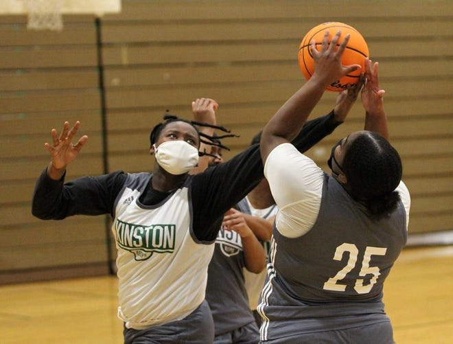 Kenya Forbes (left) tries to corral a loose ball during a recent Kinston High girls basketball practice. Forbes is one of several seniors whose leadership is key to success this season for the Vikings. [Gray Whitley / Sun Journal]
