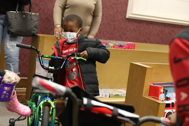 Shadore Artis, 5, picks out a bicycle at City Hall Monday, Dec. 21, out of 50 or more gifts donated to the City of Kinston after his family's house caught on fire on December 11th.