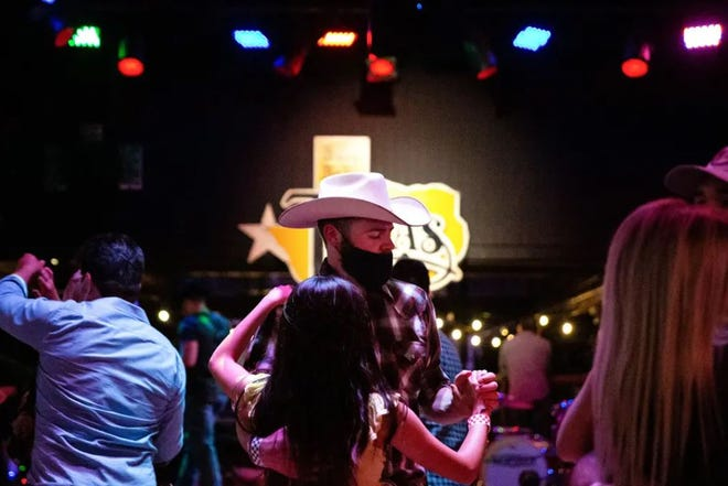 Guests dance at Billy Bob's Texas, a honky-tonk in Fort Worth. Billy Bob's was classified as a bar, but since Aug. 13 has operated under a food and beverage license.