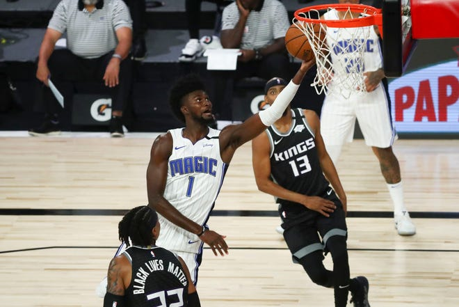 Orlando Magic forward Jonathan Isaac (1) shoots the basketball against Sacramento Kings center Richaun Holmes (22) and guard Corey Brewer (13) in August. The Magic's long-term future will depend on Isaac's continued development but they will need help from others in the short term as he recovers from a knee injury.