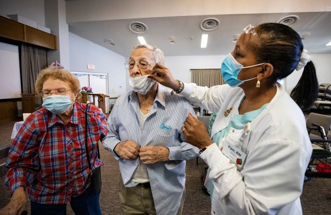 Pam Herbert, director of nursing in the assisted living facility at Florida Presbyterian Homes, helps Gerald Cook pull up his mask after he and Sue Perrin, 81, received vaccines in December.