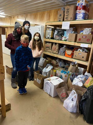 Claire Del Signore, Logan Huffman, Abby Del Signore and Libby Del Signore help unload their donations at the Faith in Action Food Pantry.