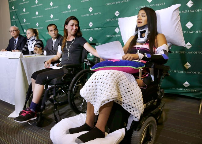 Circus acrobat Julissa Segrera, second from right, and Dayana Costa, right, are tearful as Costa reads a statement in June 2014 at Spaulding Rehabilitation Hospital in Boston. They were among the eight acrobats injured when the apparatus from which they were suspended fell, sending them plummeting to the ground during a performance of the Ringling Bros. and Barnum & Bailey Circus in Providence, R.I. Their lawyer confirmed Monday, Dec. 21, 2020, they had reached a $52.5 million settlement