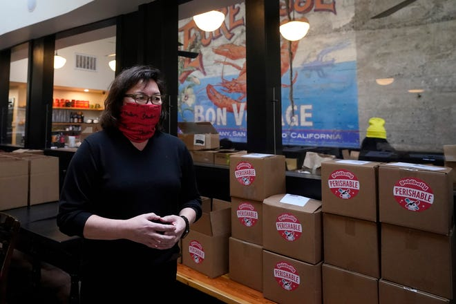 Chef Proprietor Brenda Buenviaje is interviewed next to boxes to be shipped at Brenda's French Soul Food in San Francisco on Dec. 9. [AP Photo/Jeff Chiu]