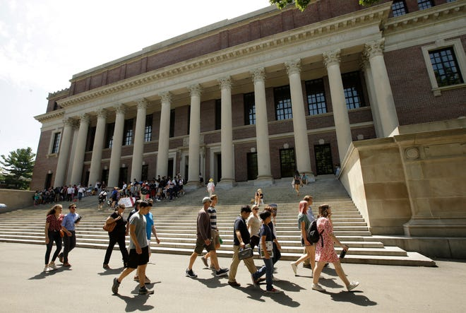 People walk past an entrance to Widener Library on the campus of Harvard University in Cambridge on July 16, 2019. [AP File Photo/Steven Senne]
