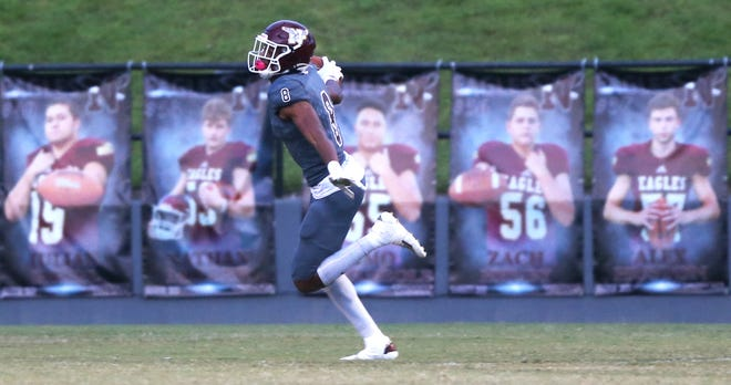 Azareyeh Thomas soars past pictures of his team after scoring during the Niceville Mosley football game at Niceville.
