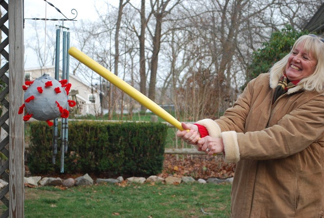 Betsy Cloyd hits the Covid pinata with glee. It was a new twist to this 45-year Christmas cookie exchange in Hingham.