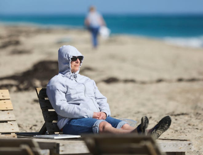 A vacationer enjoys Lake Worth beach in this file photo.