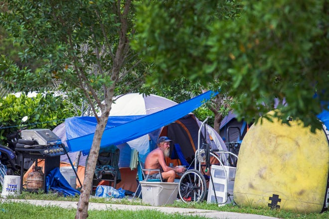 "A man sits at his encampment in John Prince Park's ""Tent City"" Friday, Aug. 21, 2020 in Lake Worth. For the past six weeks, the county has been moving homeless people out of the 726-acre park. ""It's like breaking up a village,"" said a park worker. To make the forced removal legal, county commissioners invested $8.6 million in a homeless shelter at the former county stockade off of Southern Boulevard west of Florida's Turnpike. LANNIS WATERS/PALM BEACH POST"