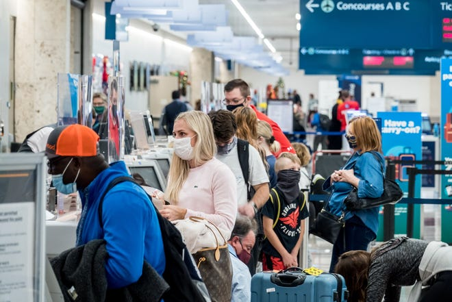 Holiday travelers check in Friday at Delta Airlines inside Palm Beach International Airport.