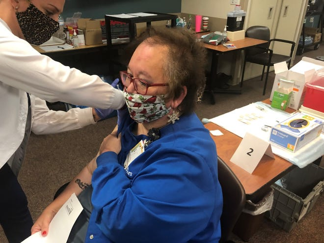 Virginia Wilson, who works in the surgical department's patient-access division at Bon Secours Southside Regional Medical Center, gets her COVID-19 vaccine at the hospital in Petersburg, Va. Tuesday, Dec. 22, 2020.