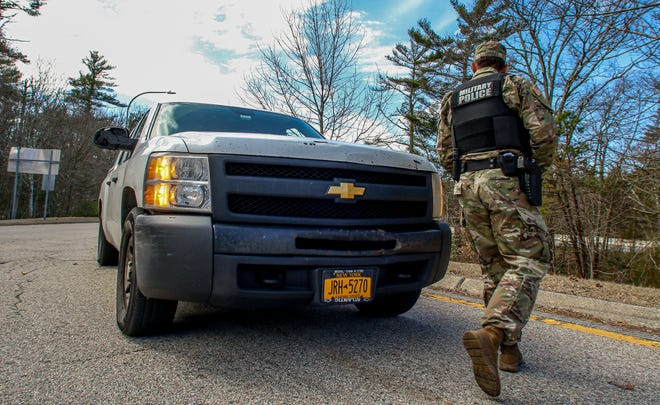 A member of the Rhode Island National Guard approaches a driver of a truck with New York license plates at a rest stop in Westerly in March.
