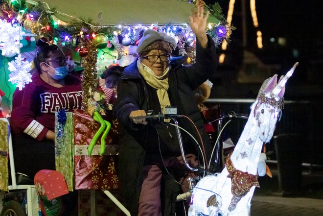 Elizabeth Wong Fontana of Pacific Pedicabs waves as she takes a family along the Waterfront Warehouse on Weber Avenue during the Unofficial Lighted Boat Parade on Dec. 5.