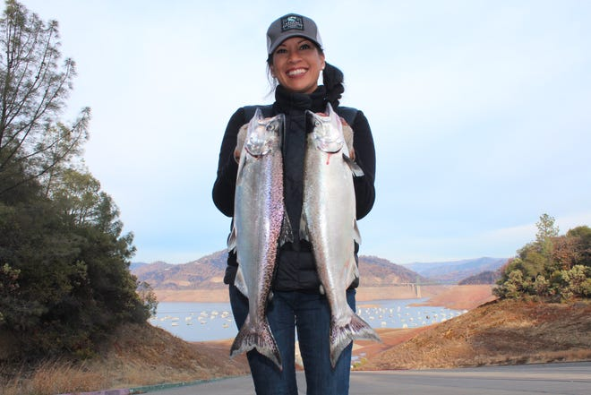 Stacy Barawed holds two salmons she and her group caught during a recent outing to Lake Oroville,