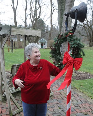 Carol Tynan shows off the dinner bell in the backyard of her 12th Street NW residence. She rings it every New Year's Day with her family to celebrate her birthday. Tynan, who turns 80 years old today, was the first baby born in Massillon on Jan. 1, 1941.