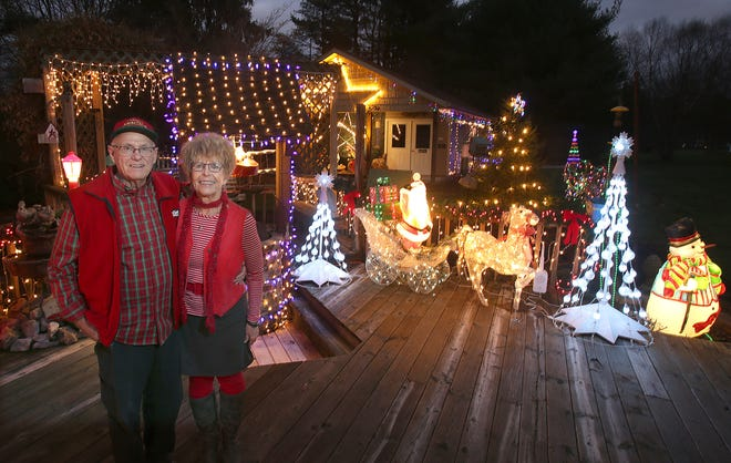 John and Betty Niebel stand outside their Roger Avenue NW home in Jackson Township home decorated with the Christmas lights they display each year. The lights went up this year thanks to neighbors and friends who helped after John underwent heart bypass surgery.