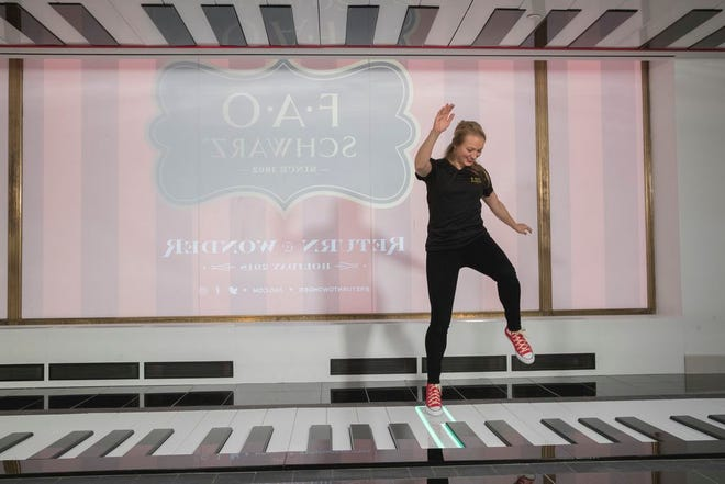 In this Nov. 13, 2018 photo, an employee plays the FAO Premium Piano Dance Mat during a media preview of the new FAO Schwarz store at Rockefeller Center in New York. A New York City family recently got to stay overnight in the store as part of a promotion between FAO and Airbnb.