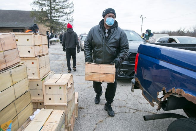Samuel Tidwell of Rockford, a volunteer with LiveFree Rockford, loads boxes of food to give to community members at New Zion Missionary Baptist Church on Tuesday, Dec. 22, 2020, in Rockford.