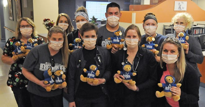 Salina Regional Health Center medical professionals hold the Bennington State Bank teddy bears after the bears spent 14 days in quarantine before they were adopted by patients at the hospital for Christmas.